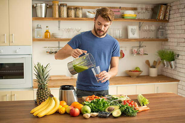 Young man making juice or smoothie in kitchen. Young man preparing fruit or vegetable smoothie or juice in his kitchen. Different fruits and vegetables on the table. Pouring green smoothie in glass. Caucasian, casual style, brown hair and beard. blender stock pictures, royalty-free photos & images