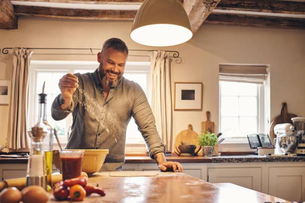 young man making pizza at home - baking bread at home imagens e fotografias de stock