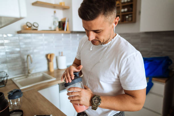 Young man making protein shake before training stock photo