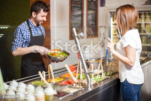 Handsome young man with a beard making a salad for a customer at a restaurant