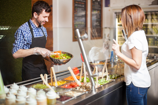 Young man making salad for a customer