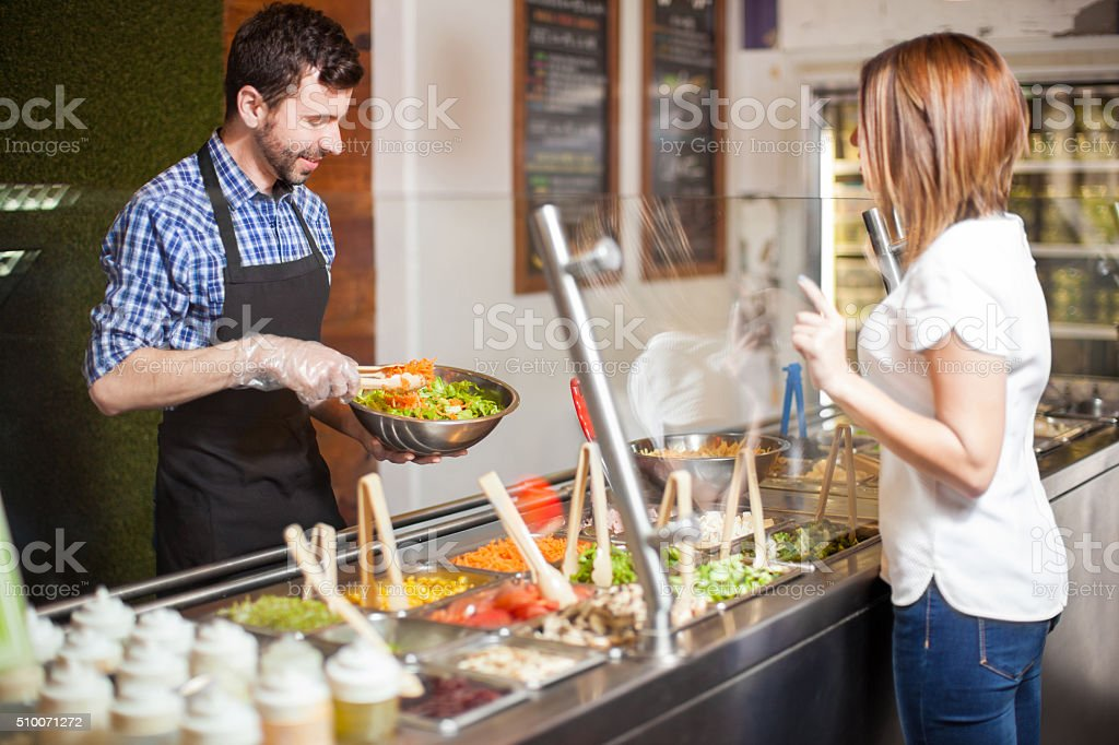 Young man making salad for a customer stock photo