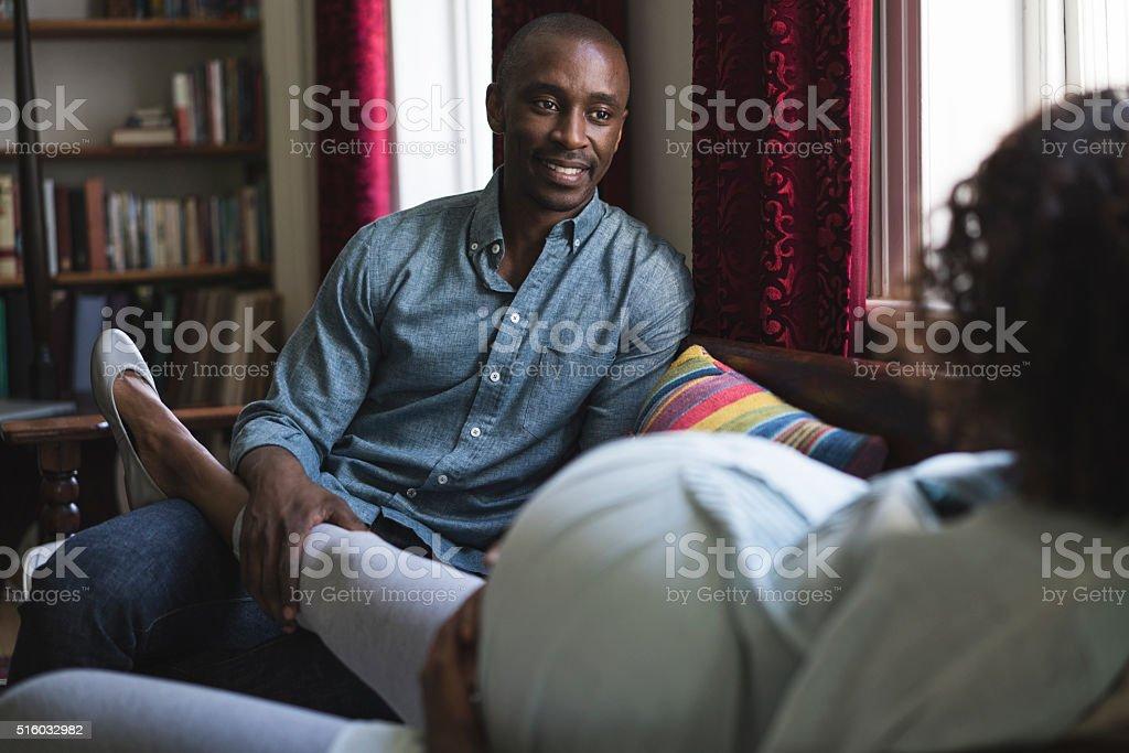 Young man massaging pregnant woman's leg at home stock photo