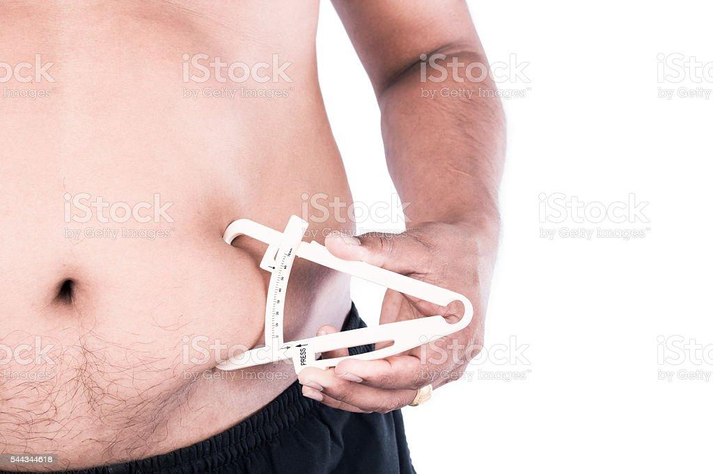 Young Man Measuring Fat Belly With Fat Caliper - foto de acervo