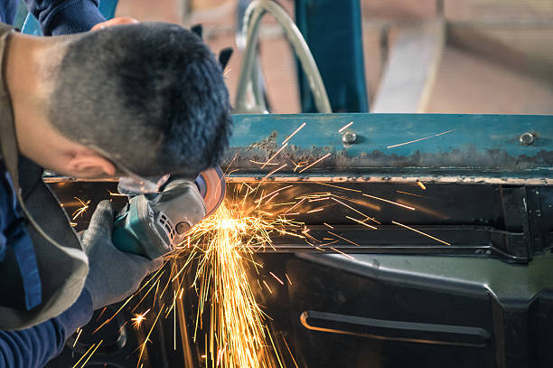 Young man mechanical worker repairing an old vintage car body stock photo