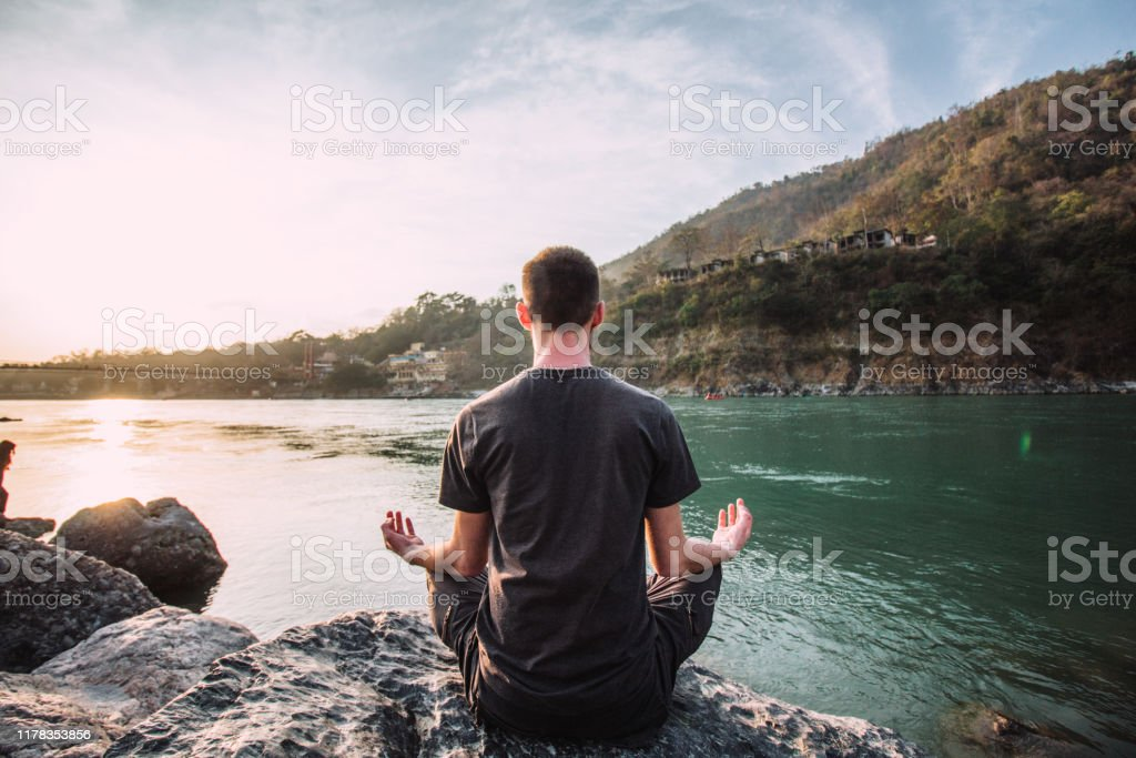 A young man meditates in a lotus position over the Ganges river in Rishikesh at the sunset. A young man meditates in a lotus position over the Ganges river in Rishikesh at the sunset. Activity Stock Photo