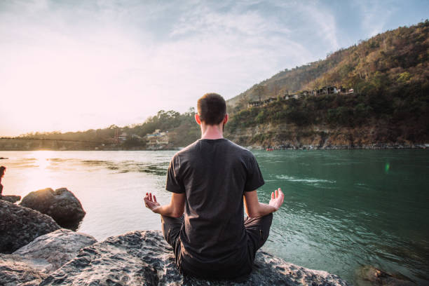 A young man meditates in a lotus position over the Ganges river in Rishikesh at the sunset. A young man meditates in a lotus position over the Ganges river in Rishikesh at the sunset. meditating stock pictures, royalty-free photos & images