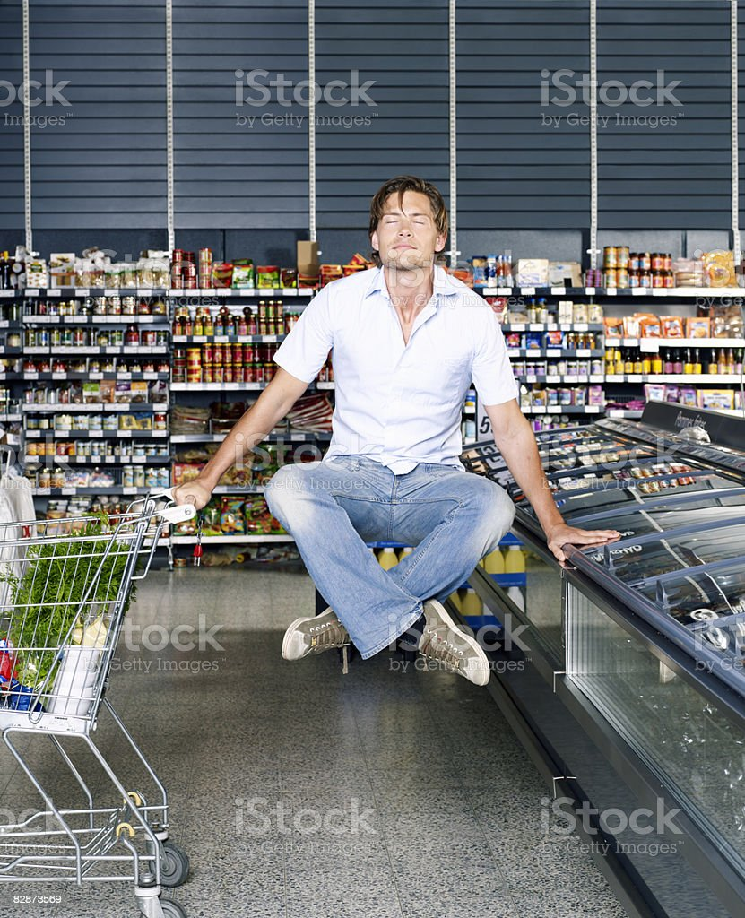 Young man meditating in supermarket, levitating.   royalty free stockfoto