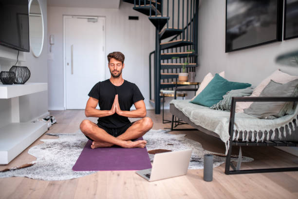 Young man meditating in the living room. stock photo
