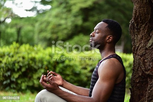 A young man sitting on the ground at a park, meditating.