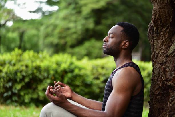 Young man meditating A young man sitting on the ground at a park, meditating. mental wellbeing stock pictures, royalty-free photos & images