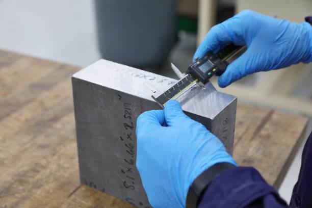 Junger Mann Fräsarbeiter misst Metallblock – Foto