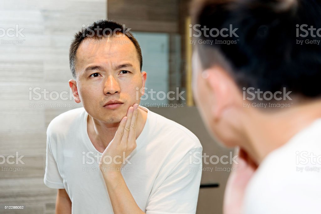 Young man morning skin care at bathroom. stock photo