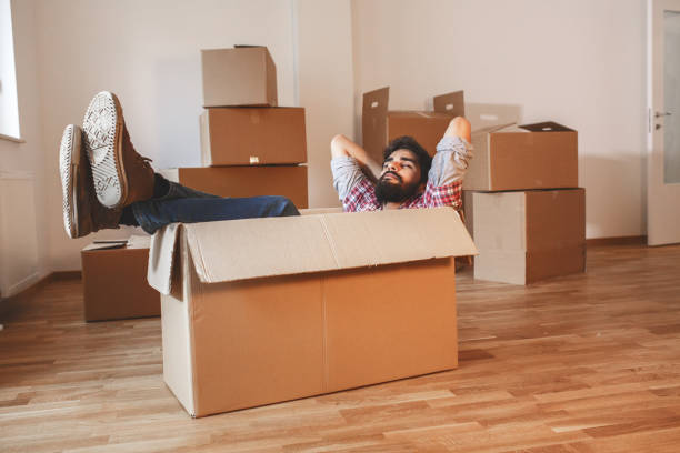 Young man moving into a new home. stock photo