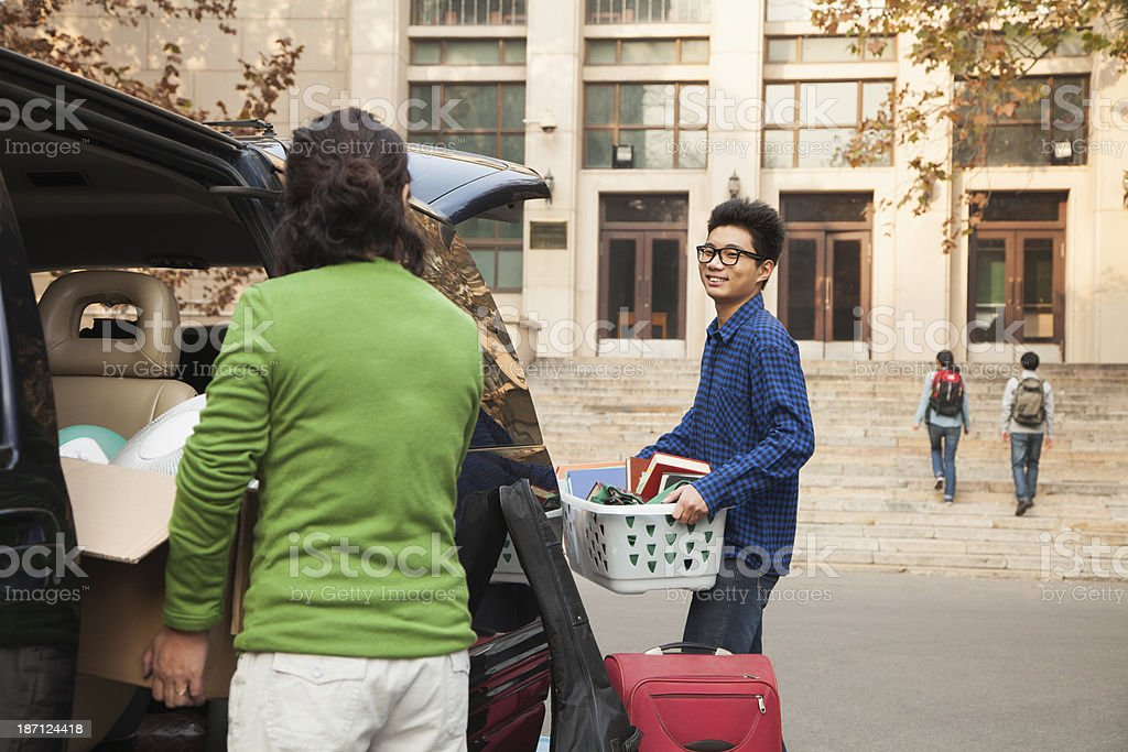 Young man moving into dormitory on college campus stock photo