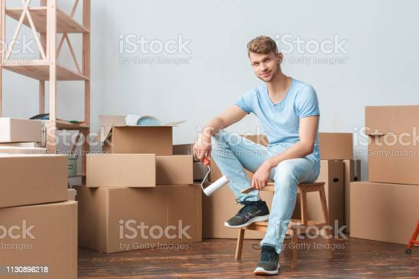 Young man moving to new place sitting holding paint roller looking picture id1130896218?b=1&k=6&m=1130896218&s=612x612&h=imotq13pntthbvuohaa jno5bhj7qwc1ybss7sld4h4=