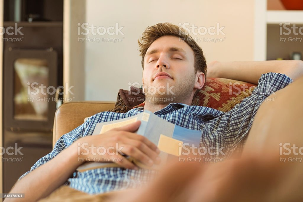 Young man napping on his couch stock photo
