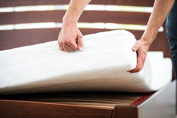 jeune homme près de lit blanc - matelas photos et images de collection