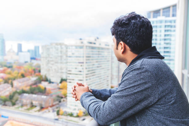 Young man newly immigrated to Canada admiring views from his apartment balcony of a highrise stock photo