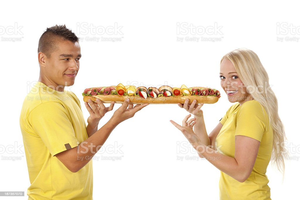 Young man offers big sandwich to his girlfriend. royalty-free stock photo