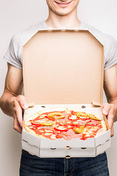 Young man offers pizza diabola. Young man offers pizza diabola. Pizza delivery courier holds two boxes in hands sergionicr stock pictures, royalty-free photos & images