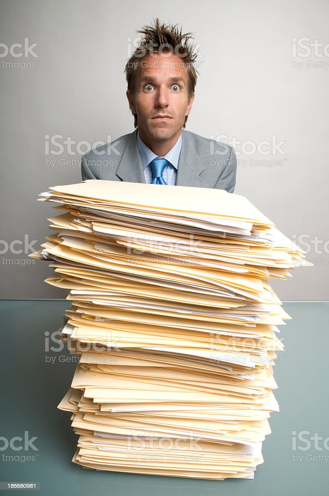 Young Man Office Worker Businessman Sitting Surprised Behind Stack Paperwork royalty-free stock photo