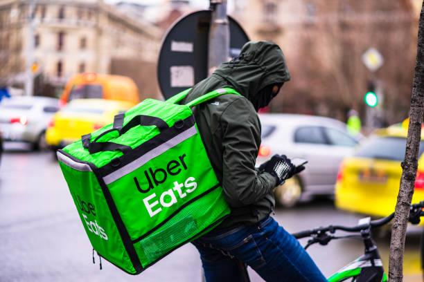Junger Mann auf einem Fahrrad mit Uber Eats Logo liefert Essen während eines regnerischen Tages in Bukarest, Rumänien, 2020 – Foto
