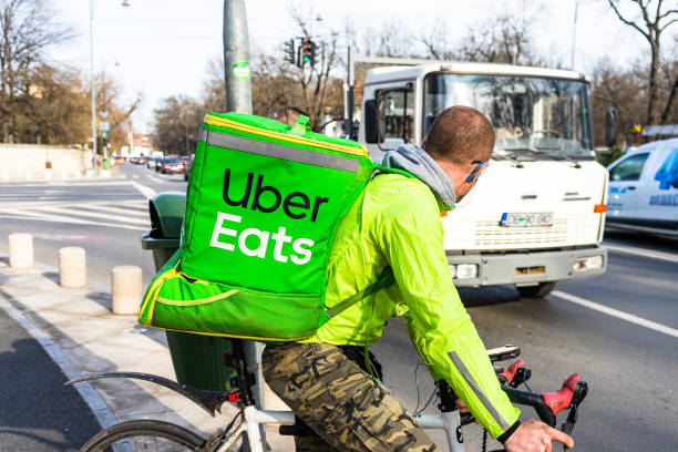Junger Mann auf einem Fahrrad mit Uber Eats Logo liefert Lebensmittel in Bukarest, Rumänien, 2020 – Foto