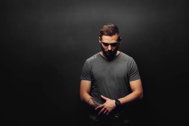 young man on a black background. - guardare verso il basso foto e immagini stock