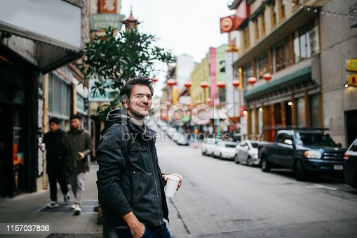 Young man standing on the sidewalk in San Francisco, Chinatown area, having a coffee break.