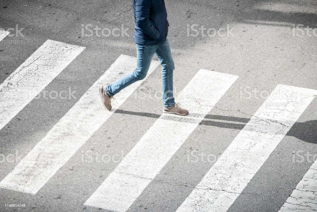 young man on a crosswalk stock photo