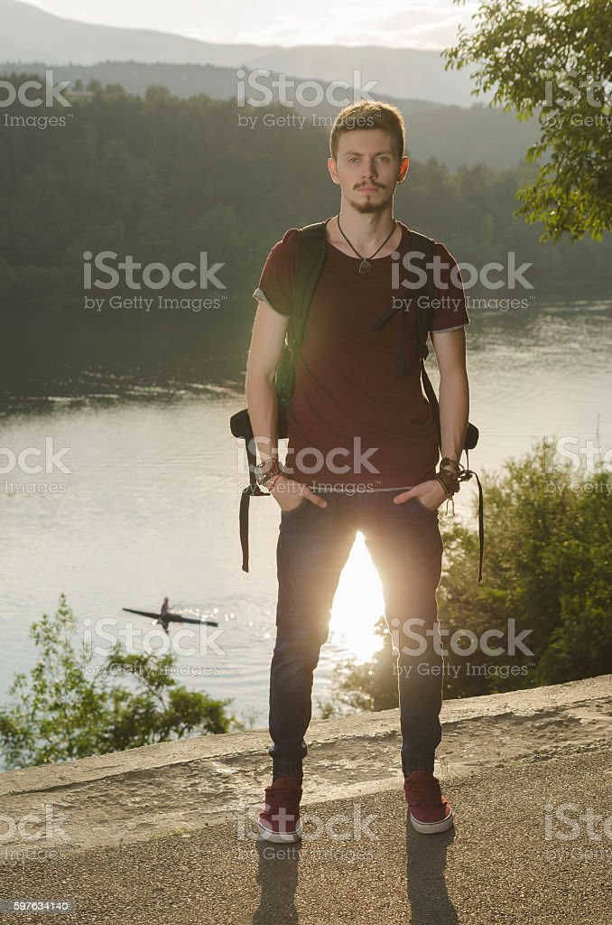 Young man on a lake with rucksack stock photo