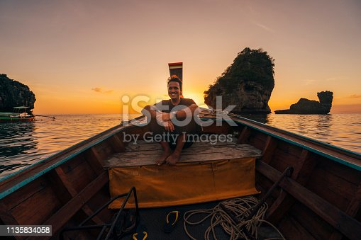 istock Young man on a longtail boat in Thailand during sunset, Phi Phi Island 1135834058