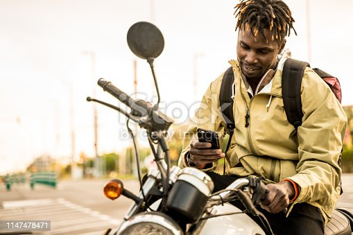 Young man on a motorbike in Barcelona streets, using his phone. He is wearing a beige jacket and carrying a backpack.
