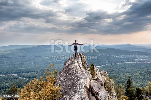 istock A young man on a mountain peak. 869675030