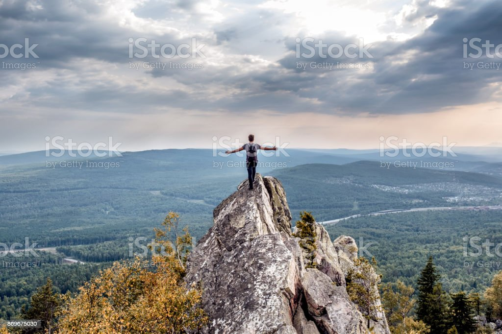 A young man on a mountain peak. stock photo