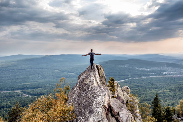 a young man on a mountain peak. - cliff stock pictures, royalty-free photos & images