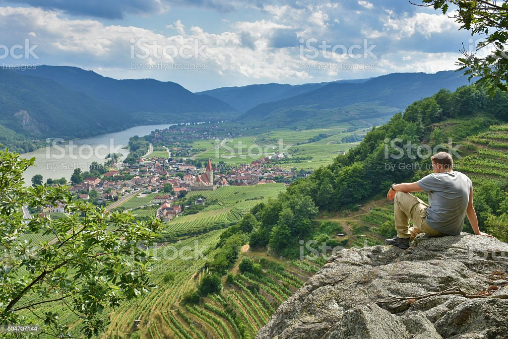 Young man on a rock above Weissenkirchen Wachau stock photo