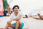 Young man sitting on the beach in the summer and looking away