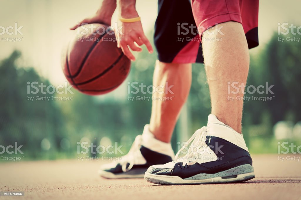 Young man on basketball court dribbling with bal stock photo