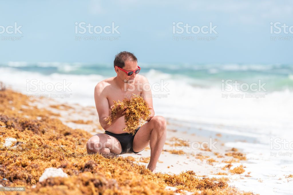 Young Man On Beach During Sunny Day With Red Sunglasses In