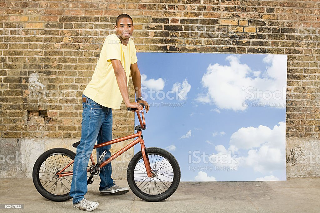 Young man on bicycle by sky backdrop stock photo