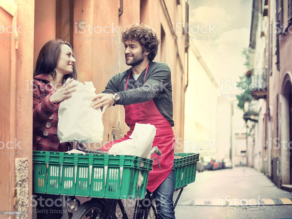 Young man on bike with apron delivering groceries to a lady stock photo