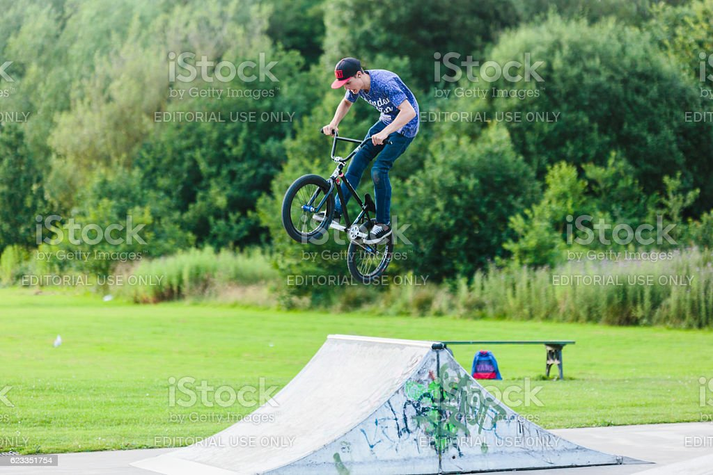 Young man on BMX jumping over ram stock photo