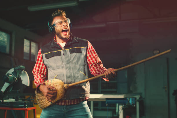 Young man on break at work has a headphones and holds a broom in his hands and pretending to play the guitar stock photo