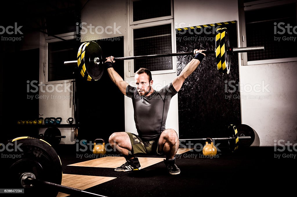 Young man on cross training lifting weights stock photo