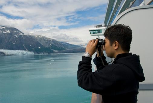 Young Man on Cruise Ship Looks Through Binoculars in Alaska