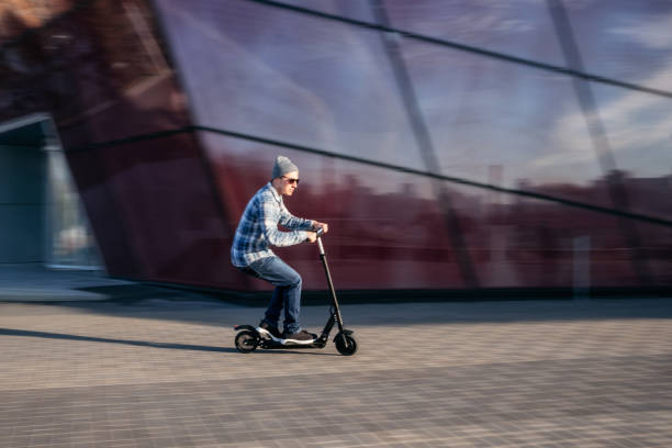 Young man on electric scooter on street stock photo