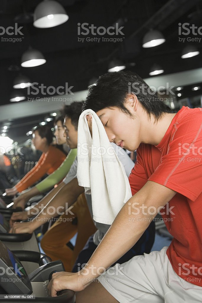 Young man on exercise bike in gym wiping sweat with towel foto de stock royalty-free