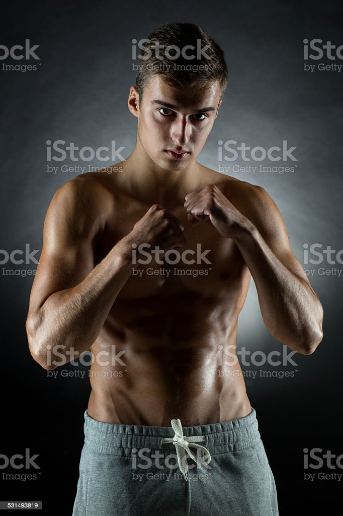 young man on fighting stand over black background stock photo